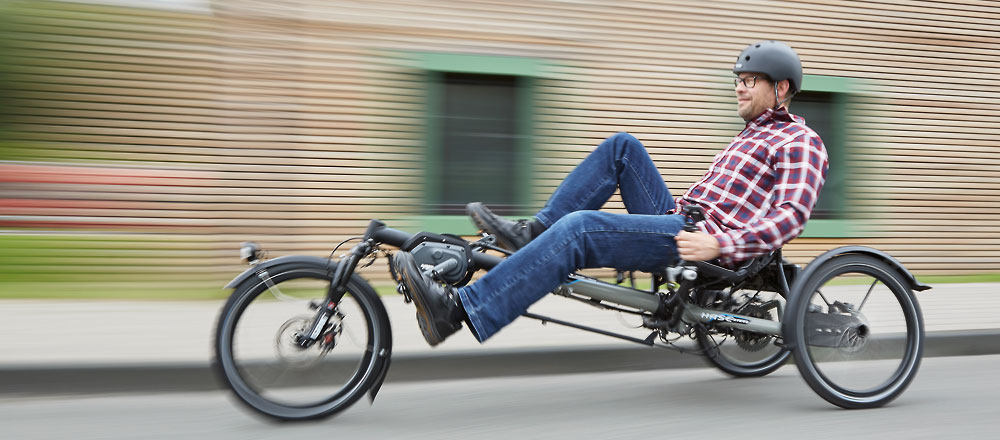 Man riding a KETTWIESEL EVOLUTION recumbent trike with e-motor