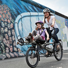 Woman and girl riding a Tandem Pino Allround past a mural