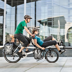 Man and woman riding a Tandem Pino Allround in a city