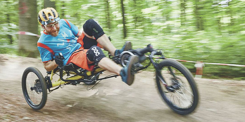 Man riding a KETTWIESEL CROSS recumbent trike on a mountain bike trail