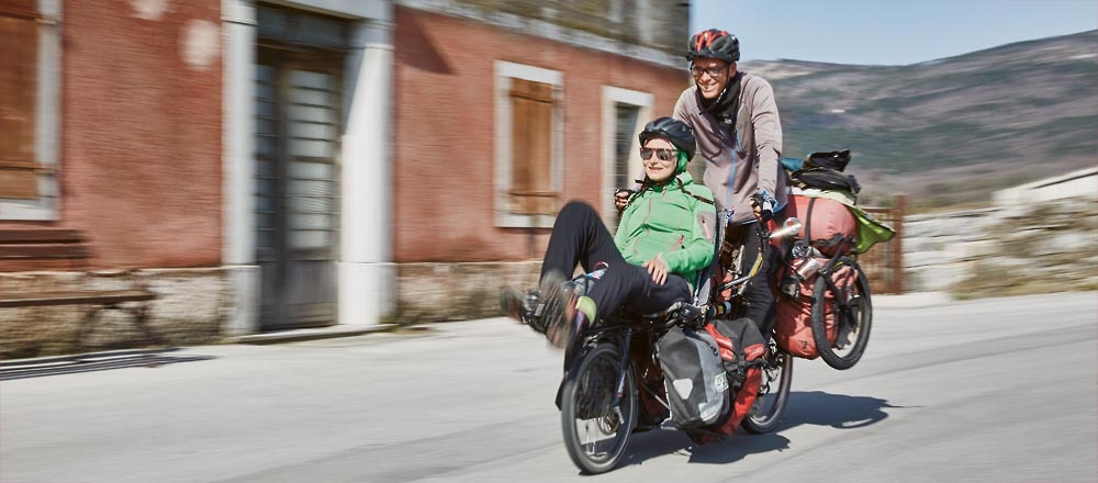 Woman and man riding a Pino Tour recumbent tandem bike with lots of cargo