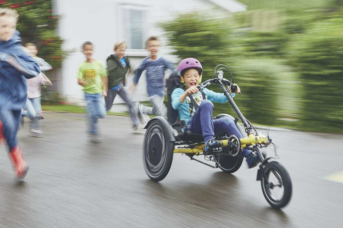 girl riding a hase trets adaptive recumbent trike with friends running alongside her