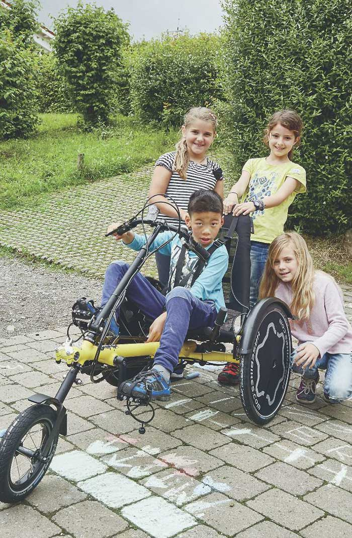 boy and friends posing with a hase trets kids recumbent trike
