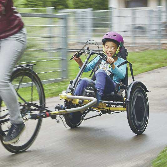 boy riding a hase trets adaptive recumbent trike as a trailer behind a parent on a bike