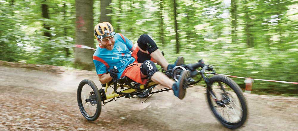 Man riding a Kettwiesel Cross Steps recumbent trike off-road down a hill in the woods