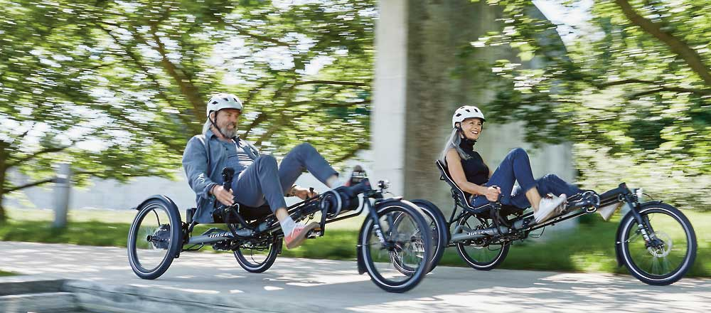 Couple riding two KETTWIESEL EVO STEPS recumbent trikes