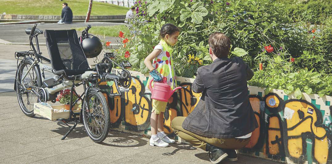 Father and daughter tending a garden using a HASE PINO tandem cargo bike to carry supplies