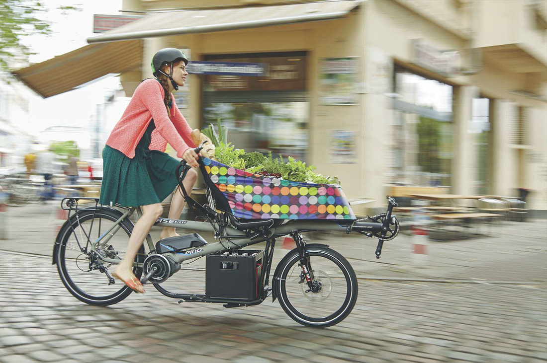 Woman riding a HASE PINO tandem cargo bike with a full load of groceries in the CITY BAG and PORTER RACK