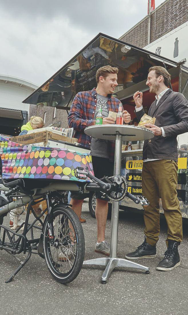 Men enjoying a market with the HASE PINO cargo bike
