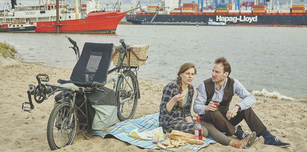 Couple enjoying a beach picnic with a HASE PINO tandem bike standing next to them on its sturdy rack
