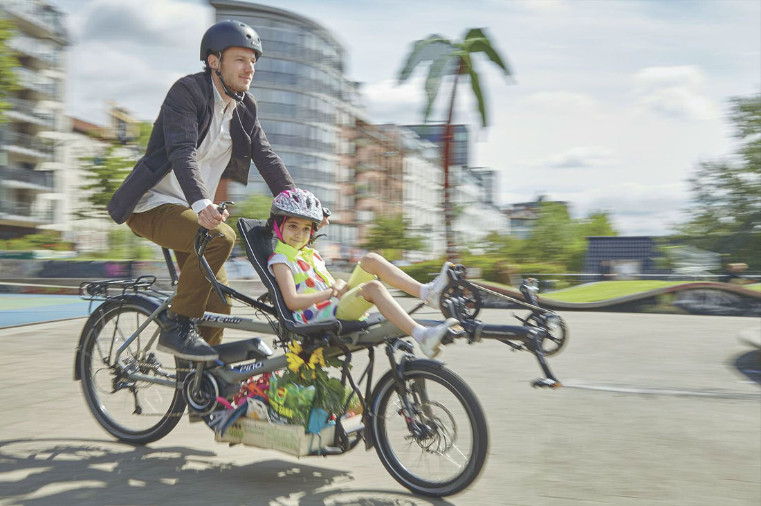 Father and daughter riding a HASE PINO tandem bike