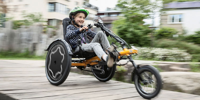 Smiling girl riding a Hase Trets Reh kids recumbent trike over a wooden walkway