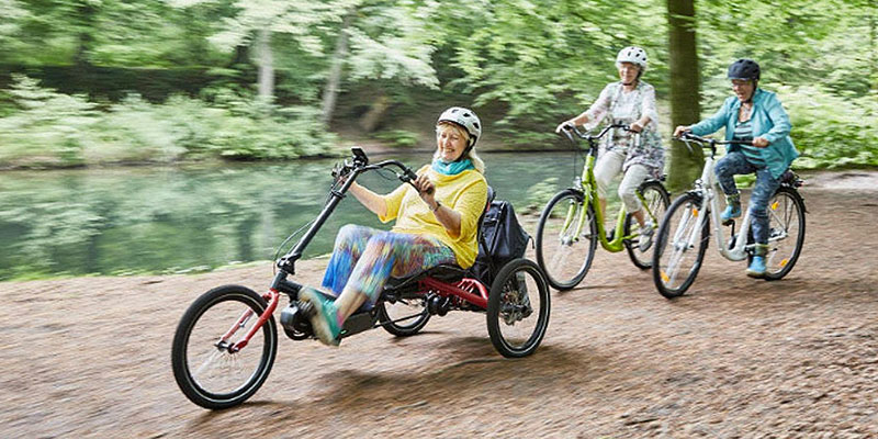 Women cycling with a woman riding a Hase TRIGO UP recumbent trike in front
