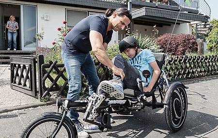 Sammy's father helps him get on the Hase Trix recumbent trike