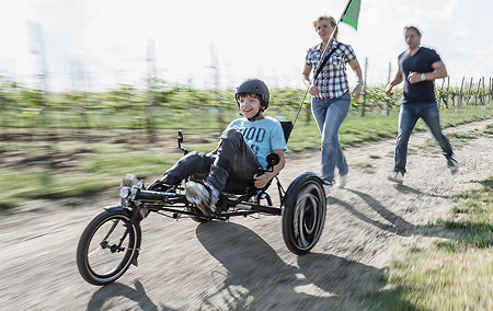 Sammy's parents chase behind him as he rides the Hase Trix recumbent trike
