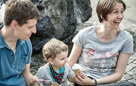 Smiling man, woman and child eating an ice cream cone