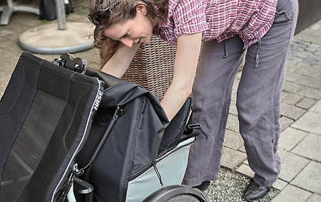 Maria reaching into the Kettwiesel Evolution recumbent trike's roller bag